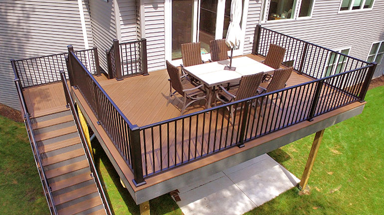 A backyard deck with Westbury Tuscany Aluminum Railing in Black Fine Texture built by PHI Decks