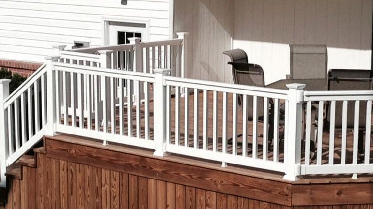 Durables Harrington t-top vinyl rail with square vinyl balusters is installed on a backyard deck and stairway in white finish with New England Post Caps