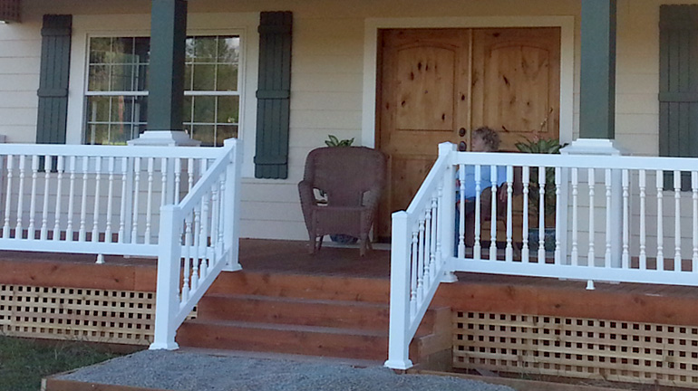 Durables premium Westport vinyl railing with standard top rail and colonial style balusters is installed on a front porch and stairway, featuring 4