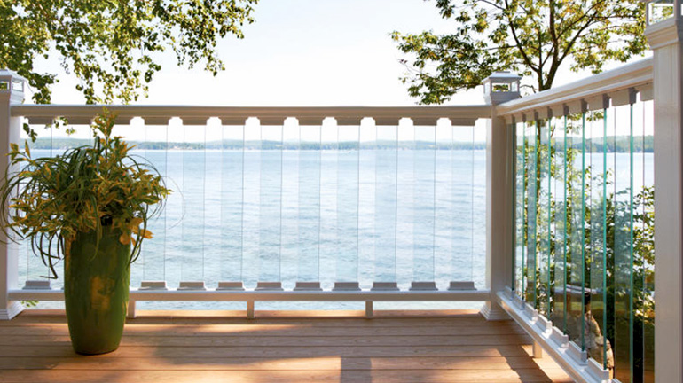 A shady composite deck overlooks the water, with the view uninterrupted by Deckorators CXT Contemporary Composite Railing, Glass Balusters, and solar post cap lights