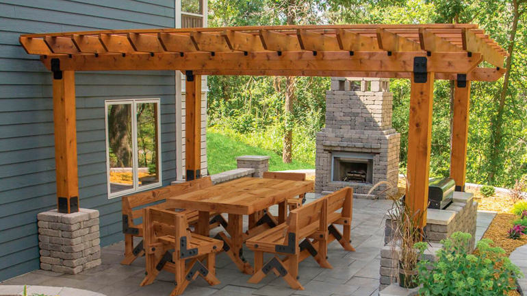 Backyard dining area with outdoor fireplace and grill are covered by a cedar pergola installed with OZCO Ironwood style post base kits, post-to-beam couplere, and rafter clips