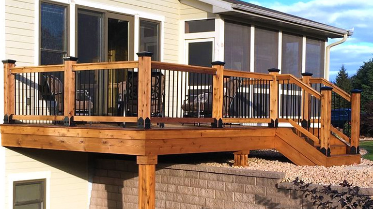 Cream-colored house with sliding door walks out onto deck adjacent to screen porch, deck features cedar rails and posts, posts attached with OZCO Laredo Sunset Style Post Base Kits