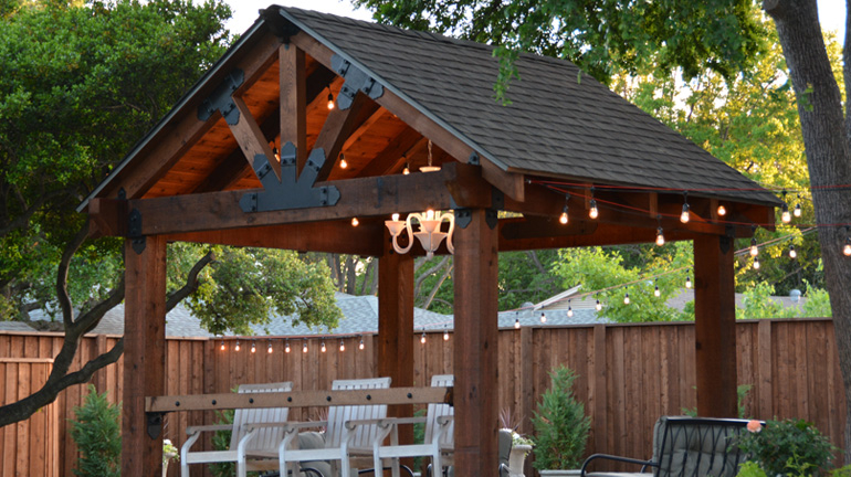 A backyard pavilion, OZCO Project #210 shown complete and adorned with hanging lights and a custom outdoor chandelier
