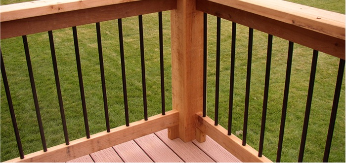 a cedar deck railing with aluminum round balusters mounted between the rails