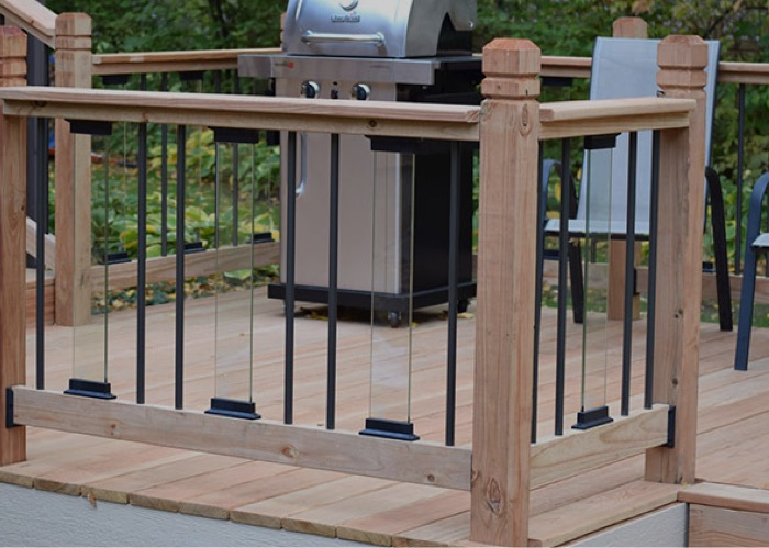 A cedar deck railing with glass and aluminum balusters and a grill next to the house in the background