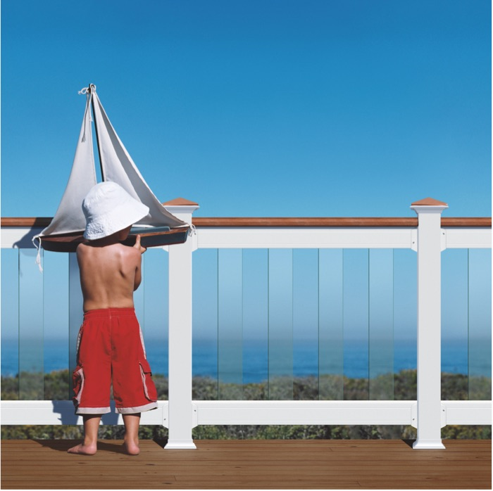 a boy with a sailboat next to a composite railing with Deckorators Glass balusters and connectors