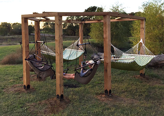 a women chilling in a hammock attched to a arbor build with OZCO wood ties