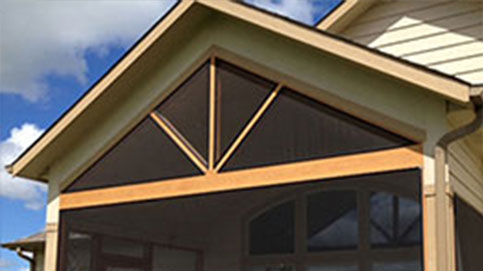 A brown a-frame home with a screened in porch with SCREENEZE®.