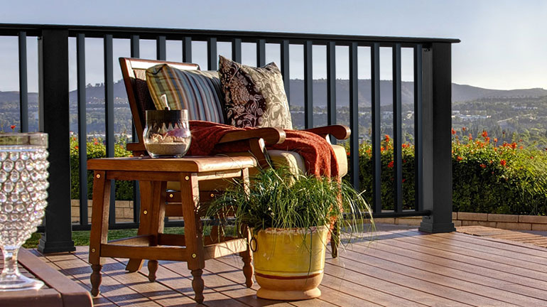A wood deck chair sitting on a wood deck surrounded by Timbertech Evolutions Contemporary railing on a sunny day.