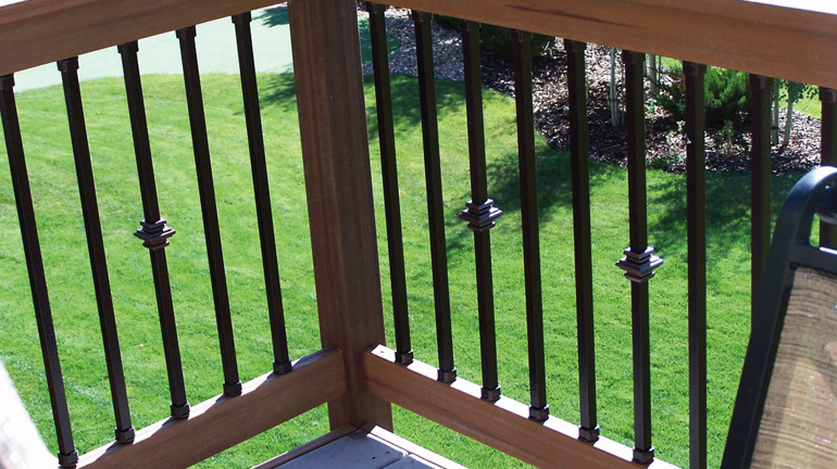 Dekor Dark Copper Vein Square Balusters and Casey Collar Balusters are installed between wood rails using durable aluminum connectors