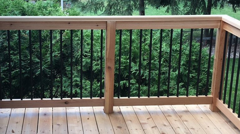 Wood deck with DecksDirect brand black balusters installed between cedar rails and posts