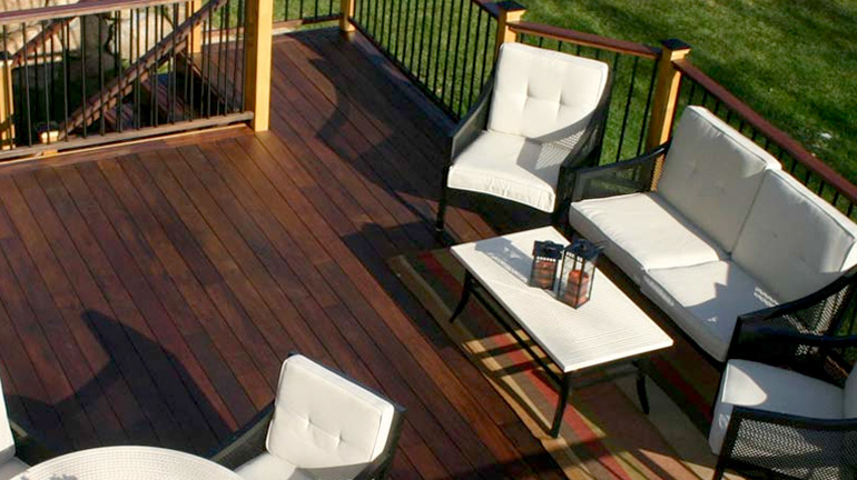 A deck with white outdoor furniture shows a hardwood deck surface and railing after treatment with IPE Oil from DeckWise