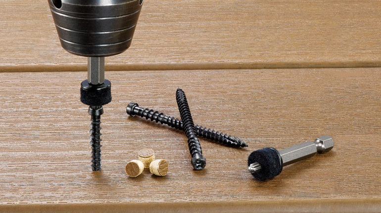 Close up of the components of the FastenMaster Cortex Hidden Fastening System: 2-1/2in screws, plugs made from real composite or PVC decking, and a setting tool with industrial-grade felt