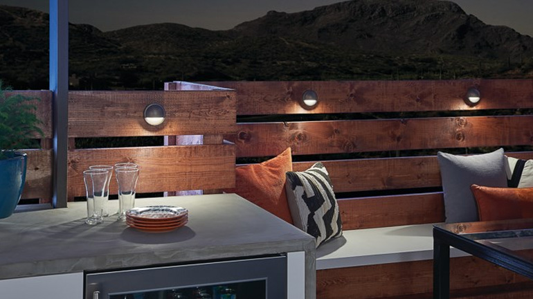 The perimeter of an outdoor wet bar is illuminated with Kichler Half Moon Rail Lights for safety and ambience