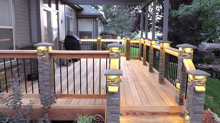 A backyard deck features NextStone post covers in Pewter with Gray SlateStone post cover caps, post cap light kits, and down light kits
