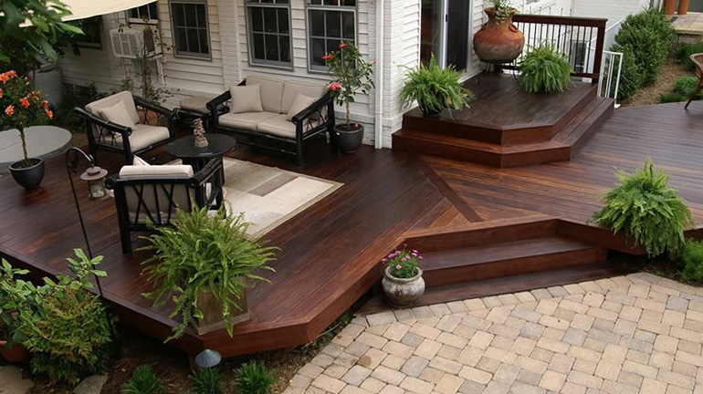 A hardwood deck decorated with furniture and potted ferns is protected with Penofin Penotrating Oil