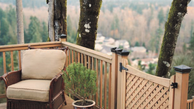 A wood deck with wood railing and a wood gate has black glass post caps by Woodway installed on 4x4 posts