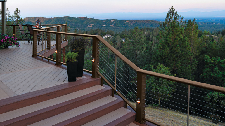 A multi-level deck with expansive views features TimberTech Evolutions Rail in Traditional Walnut finish with Cable infill and DeckLites rail lights in Architectural Bronze
