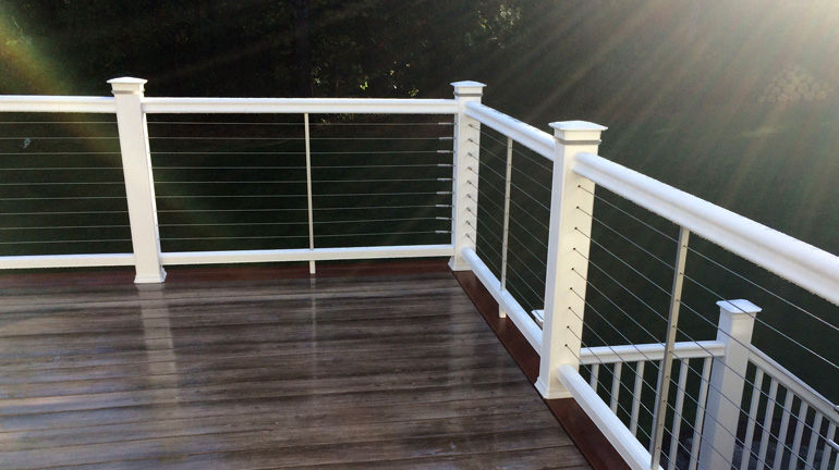 A picture-framed deck features AZEK TimberTech RadianceRail in Coastal White installed with CableRail by a DecksDirect customer, also utilizing DeckLites Post Light Modules and intermediate pickets