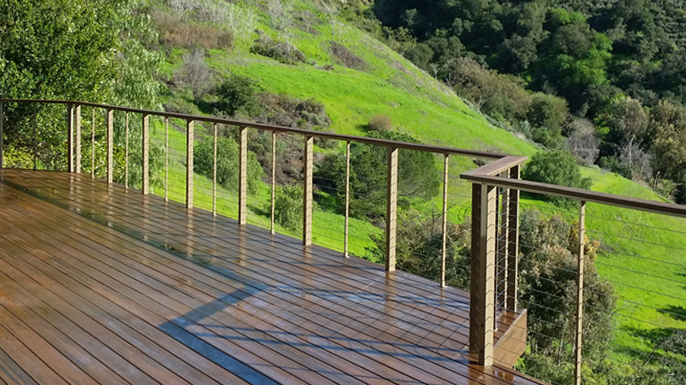 A composite deck overlooking a lush green hillside has Feeney CableRail installed to provide a clear view of the scenery