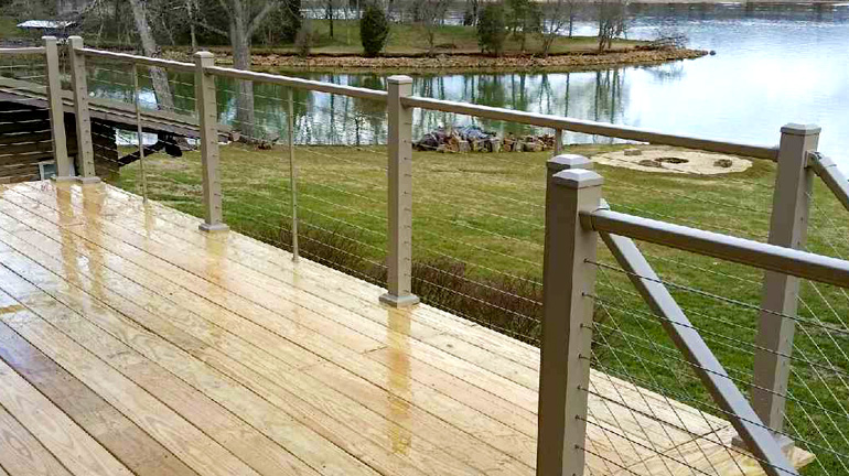 A lakeside deck shown after a rain has Prestige Cable Railing in Maple Cream finish