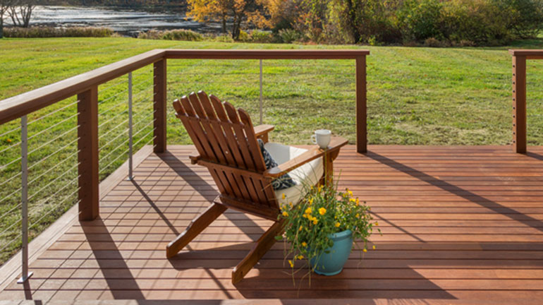Feeney CableRail is installed on a wooden deck overlooking water and fall trees with an Adirondack chair and potted plant on the deck