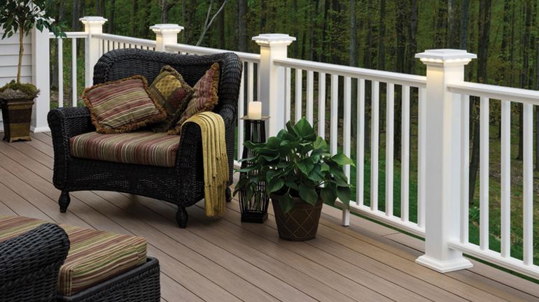 AZEK Premier Rail in White is installed with post sleeves and Post Light Modules on a deck featuring lounge furniture and potted plants that overlooks a wooded area