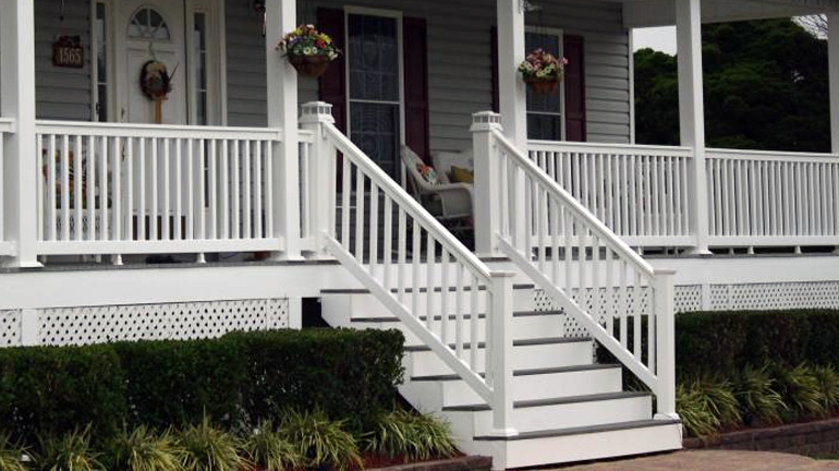 Durables Harrington t-top vinyl rail with square vinyl balusters is installed in white on a front stairway and wraparound porch