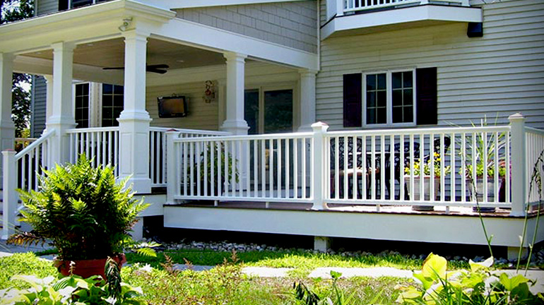 Gray house with front deck featuring Deckorators Colonial CXT Composite Railing in white with square balusters and copper-top post caps