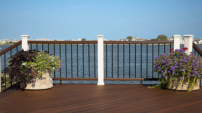 Waterside deck with Trex Transcend white post sleeves, Rails in Vintage Lantern, and classic black aluminum round balusters