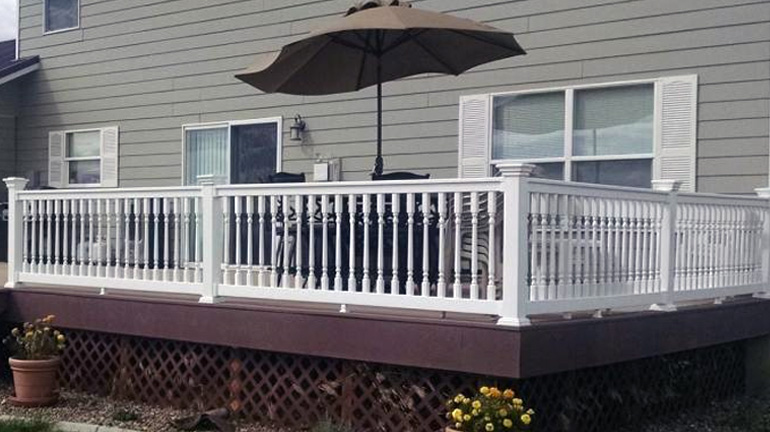 Durables Ashington t-top vinyl rail with colonial-style balusters and Federation Post Caps is installed on a dark brown deck outside of a gray house