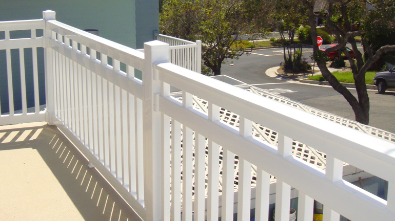 Durables Dorset three-rail vinyl railing is installed on an upper balcony in white with 4