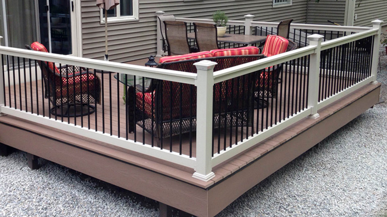 Durables Kirklees T-style top vinyl rail in tan with black round aluminum balusters is installed on a low backyard deck with a dining table and lounge set