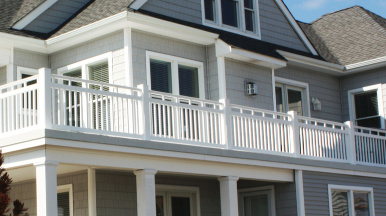 A second-floor balcony features Fairway Contour Mission Style Vinyl Rail in White with 6-1/2