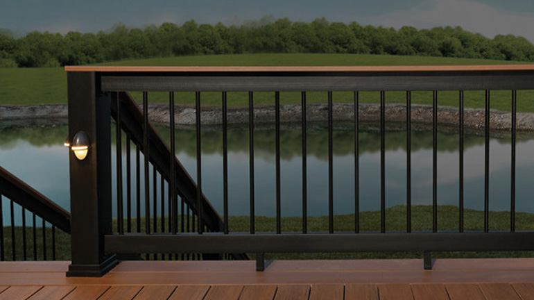 TimberTech Evolutions Rail Builder Style in Black with a light brown deck board top rail is installed on a deck overlooking a pond; AZEK Rail Lights in Architechtural Bronze are installed on a Black Evolutions Rail Post Sleeve