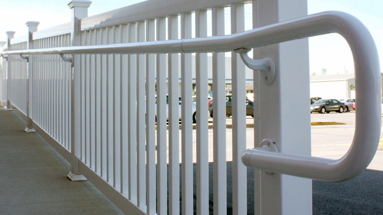 A white vinyl handrail reinforced with aluminum adds security to a ramp