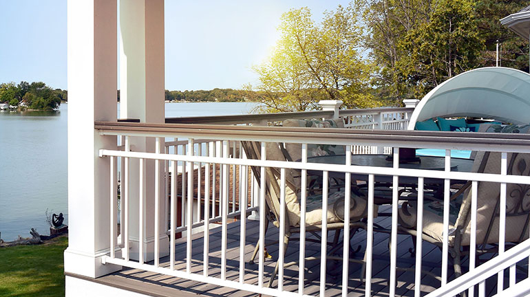 A composite deck with White Aluminum Railing and Afco Natchez Traditions Series Alumum columns overlooking a lake view.