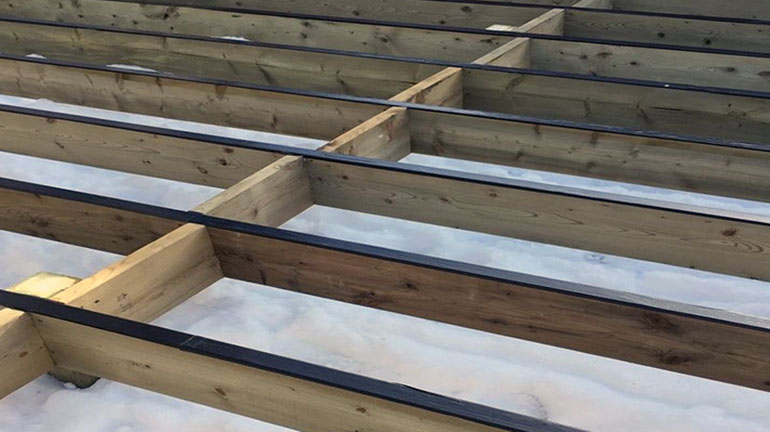 A deck joists protected with flashing before the deck boards are installed