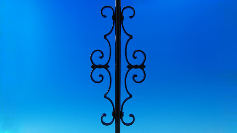 Black Centerpiece Accessory by Deckorators installed on a Rond black baluster infront of a blue background.