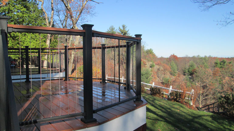 FortressCable V-Series Railing is installed on an angular deck overlooking a wooded landscape, the deck railing features Black Sand posts and rails, plus utilizes a deck board drink rail