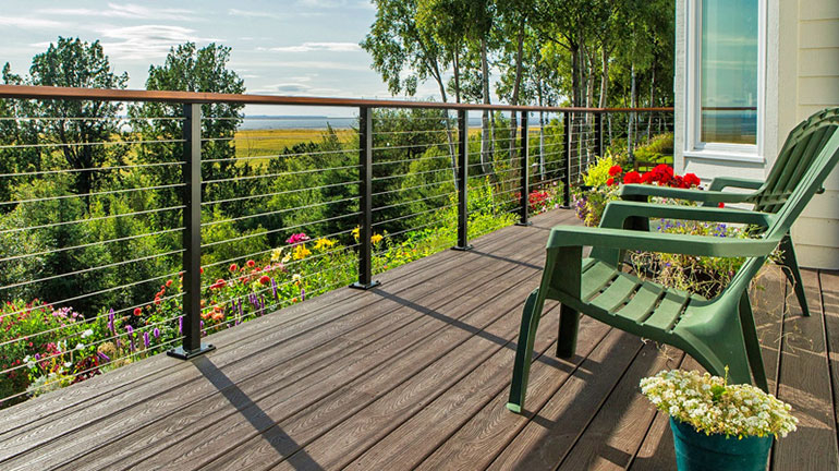 Two green chairs sit on a deck with a view over the treetops and wildflowers. The Feeney CableRail and custom metal railing keeps the deck safe without obstructing the view.