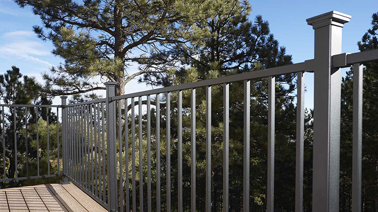 Fortress FE26 Steel Panel Railing system on a composite deck with tree tops in the distance