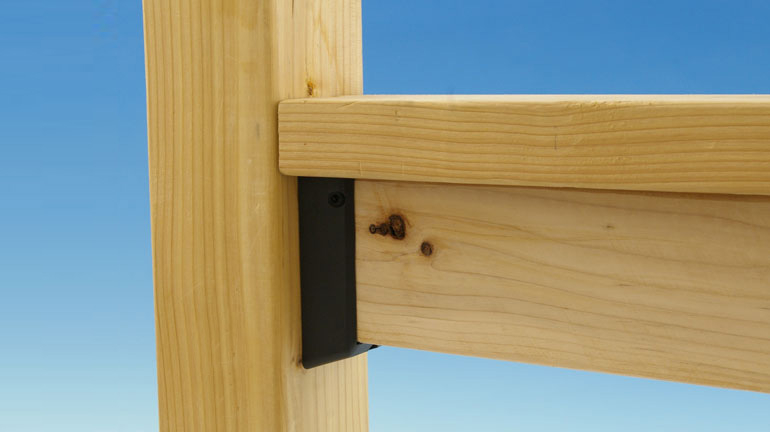 Level fortress rail connector installed in wood deck railing infont of a blue background.
