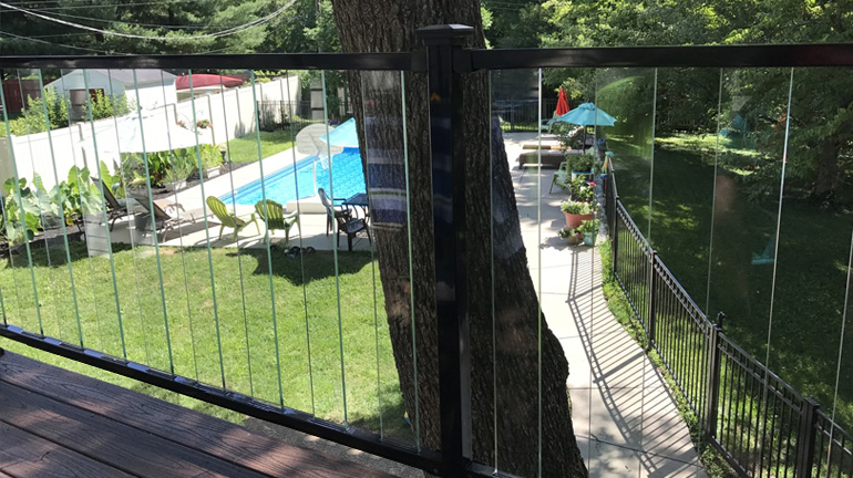 Composite deck overlooks a backyard pool, the view made possible because of the Fortress FE26 Iron Rail system in gloss black with clear PureView Glass Balusters