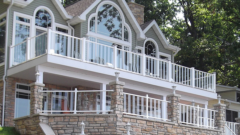 White Fortress AL13 aluminum railing with clear glass balusters provide an unobstructed view from a stately gray house with large picture windows