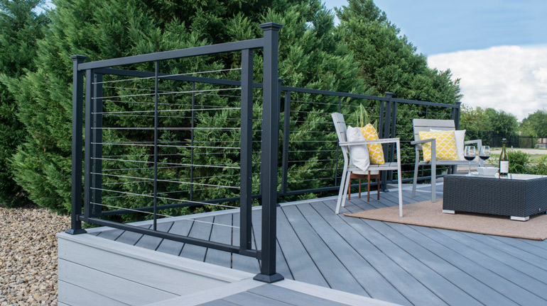 Fortress FE26 Horizontal deck installed on a grey composite deck with upholstered chairs looking over some green trees