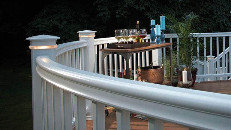 Curved AZEK RadianceRail railing in White wiht a drink cart filled with wine for a perfect summer evening