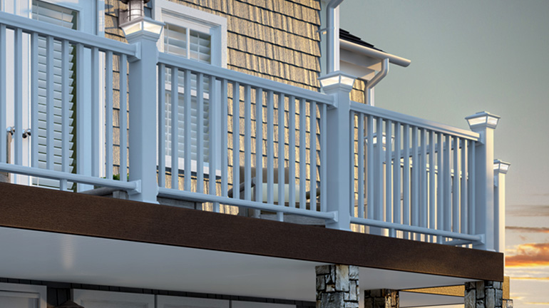 White Solar VersaCaps by Deckorators are illuminated on top of white deck rail posts in front of a gray house