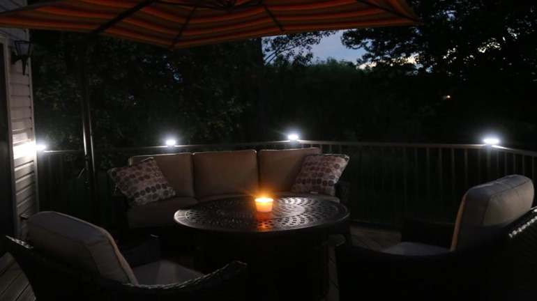 A night view of lounge furniture on a deck illuminated by a candle and post cap lights from Magena Star Lighting by Westbury