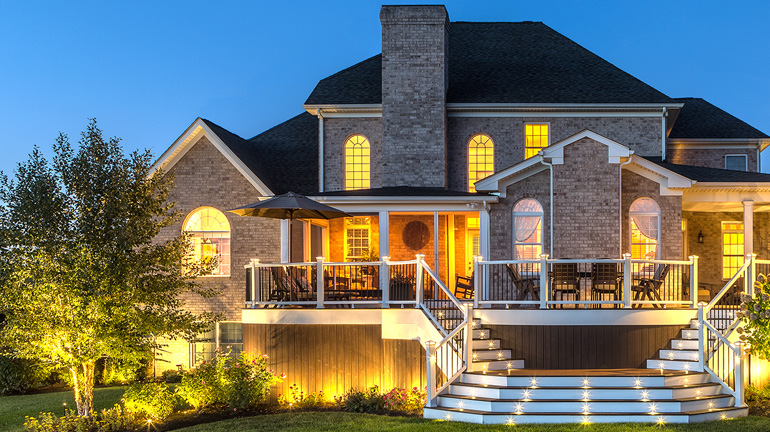 The deck on large brick house is shown at dusk with Trex landcape lighting and LED deck lighting